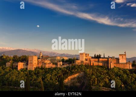 Luna e golden sunset sulla collina alhambra palace complesso fortificato Granada Spagna con Snow capped sierra nevada Foto Stock
