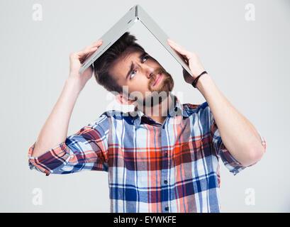 Giovane Azienda laptop sulla sua testa come il tetto della casa isolata su uno sfondo bianco. Ricerca di Foto Stock