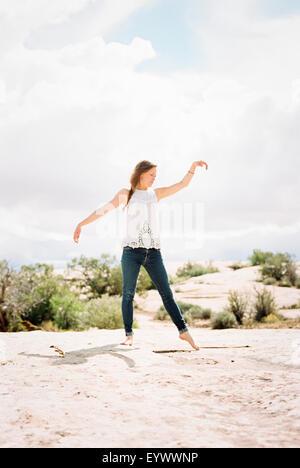 A piedi nudi donna che indossa jeans con le braccia sollevate. Foto Stock