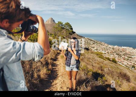 Eccitato giovane donna che mostra mappa e in posa per il suo fidanzato tenendo le sue foto con la fotocamera digitale. Foto Stock