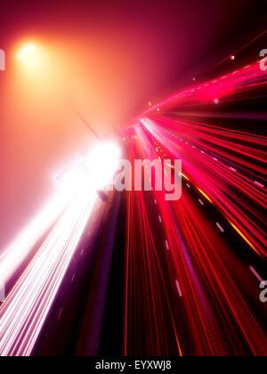 Luce colorata sentieri della trafficata autostrada traffico su una notte di nebbia, Highway 401, Toronto, Ontario, Canada. Foto Stock