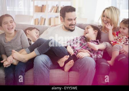 Famiglia caucasica giocando sul divano Foto Stock