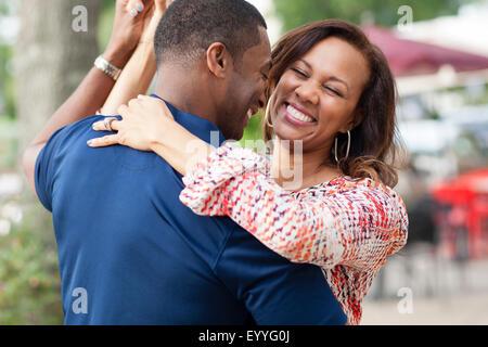 Sorridente coppia danzante sul marciapiede Foto Stock