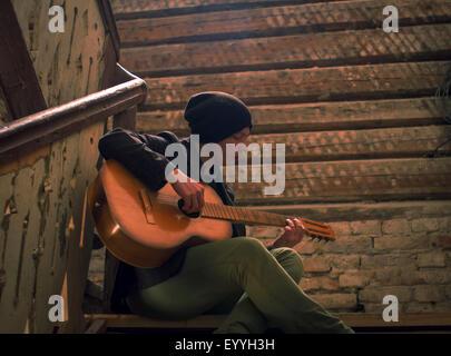 Uomo caucasico suonando la chitarra su scala