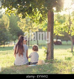 La madre e il bambino seduto sotto la struttura durante il periodo estivo il tempo libero Foto Stock