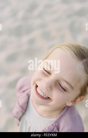 Ritratto di un sorridente ragazza giovane, in piedi su una spiaggia di sabbia.