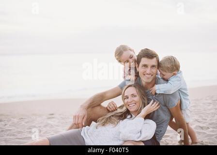 Abbracciando giovane con il loro figlio e figlia su di una spiaggia di sabbia, guardando la telecamera, sorridente. Foto Stock