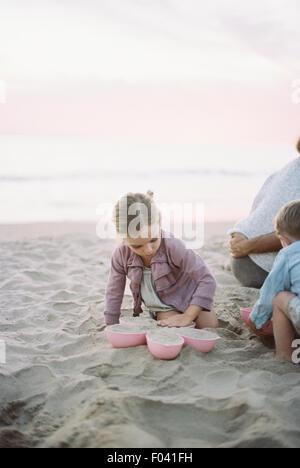 Ragazzo e ragazza che gioca nella sabbia sulla spiaggia accanto a un adulto giovane. Foto Stock