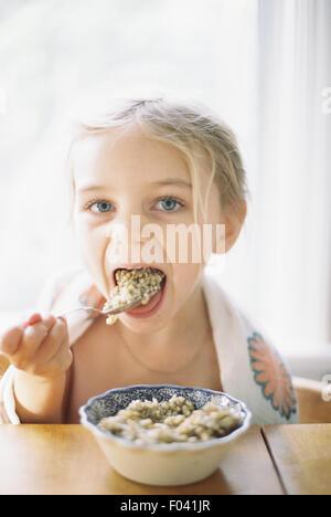 Giovane ragazza seduta a tavola a mangiare la prima colazione da una ciotola. Foto Stock