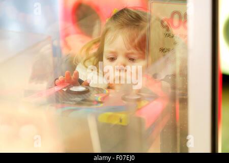 Un bambino che gioca su una sala giochi macchina Foto Stock