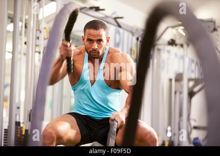 Giovane uomo che lavora fuori combattimento con corde in una palestra Foto Stock