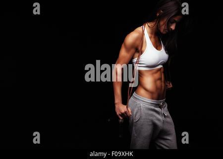 Immagine di bodybuilder femminile azienda corda da salto guardando verso il basso. Giovane donna fitness con corpo Foto Stock