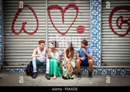 Gruppo di amici, seduto sulla mensola, parlando Foto Stock