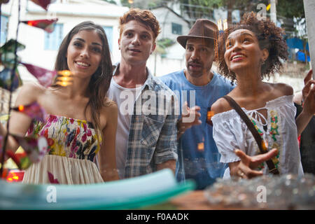 Gruppo di amici alla ricerca nella finestra del negozio Foto Stock