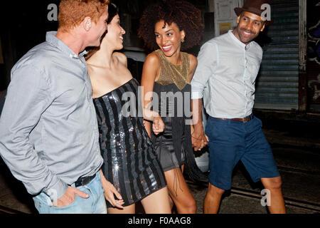 Quattro amici camminando lungo la strada insieme di notte Foto Stock
