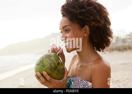 Ritratto di giovane donna di bere latte di cocco sulla spiaggia di Rio de Janeiro, Brasile