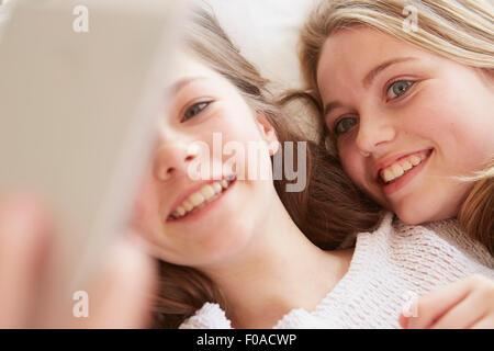 In prossimità di due ragazze giacente sul letto prendendo selfie dello smartphone Foto Stock