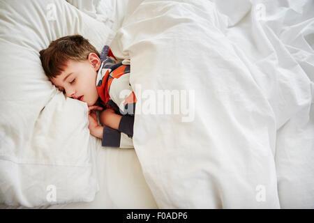 Giovane ragazzo dormire nel letto Foto Stock
