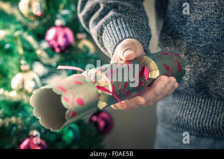 Persona in possesso di Christmas Cracker Foto Stock
