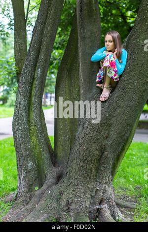 Poco carino ragazza seduta su un albero. Foto Stock