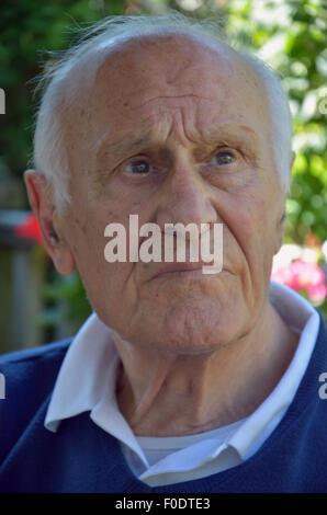 Un uomo anziano che soffrono di demenza seduta tranquillamente cercando perso nei suoi pensieri. Foto Stock