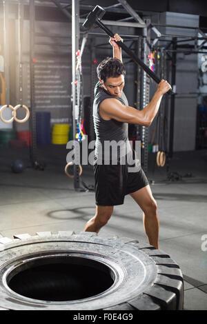 Giovane uomo di martellamento dei pneumatici di grandi dimensioni in palestra Foto Stock