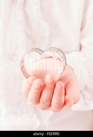 Bambina di contenimento a forma di cuore cookie cutter in mano. Immagine concettuale di infanzia, di amore e di Foto Stock