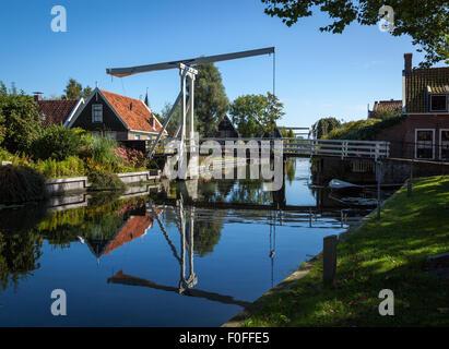 Tradizionale impostazione rurale di un piccolo villaggio in Olanda, Paesi Bassi. Piede di sospensione Bridge crossing over teh fiume. Foto Stock