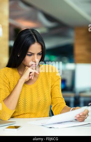 Ritratto di una bella imprenditrice la lettura dei documenti di office Foto Stock