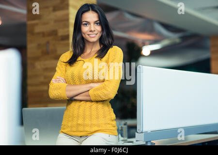 Ritratto di un sorridente imprenditrice in piedi con le braccia piegate in ufficio e guardando la fotocamera Foto Stock