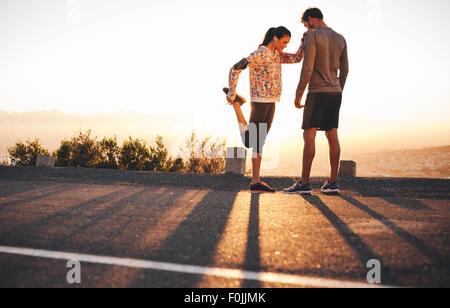 Colpo all'aperto di montare i giovani praticanti di jogging stretching prima di correre insieme in mattina. Giovane Foto Stock