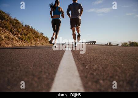 Vista posteriore di due giovani una formazione insieme sulla strada. L uomo e la donna sulla corsa mattutina sul Foto Stock