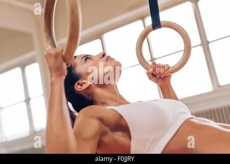 Immagine ravvicinata di un forte giovane donna facendo pull-up con anelli di ginnastica. Fitness atleta femminile per gli esercizi in palestra. Foto Stock