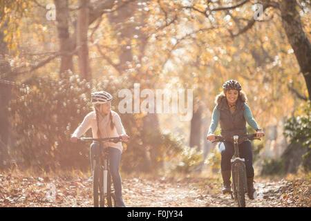 Madre e figlia in bicicletta sul percorso nel bosco Foto Stock