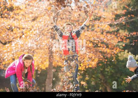 Giocoso ragazzi e una ragazza correre e saltare in foglie di autunno Foto Stock