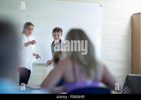 Insegnante in classe con scolaro a whiteboard Foto Stock