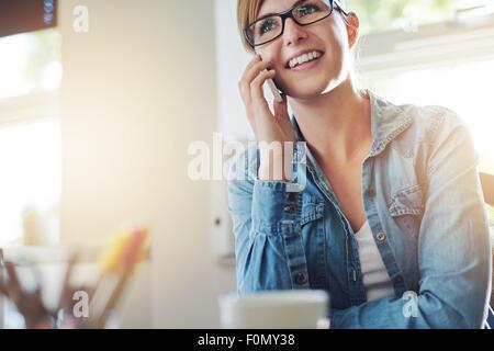 Vicino la giovane donna ufficio per parlare a qualcuno sul suo telefono cellulare mentre guardando in lontananza Foto Stock