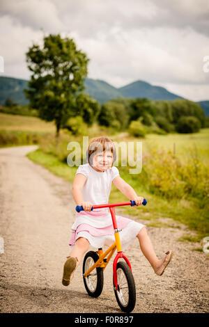Bambino Piccolo che guida i suoi abeti bicicletta su strada rurale outdor in natura Foto Stock