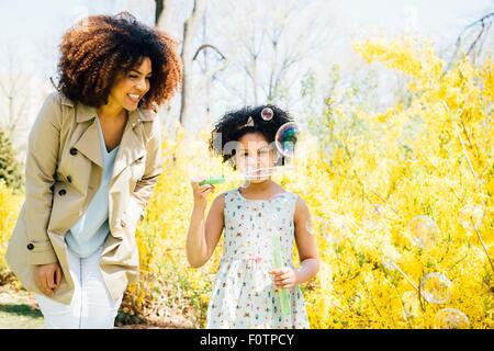 Vista frontale della madre e figlia a soffiare bolle Foto Stock