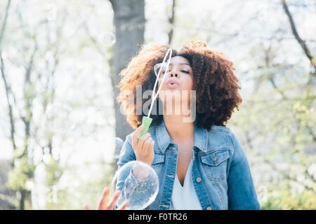 Vista frontale della metà donna adulta soffiare bolle a occhi chiusi, guardando verso l'alto Foto Stock