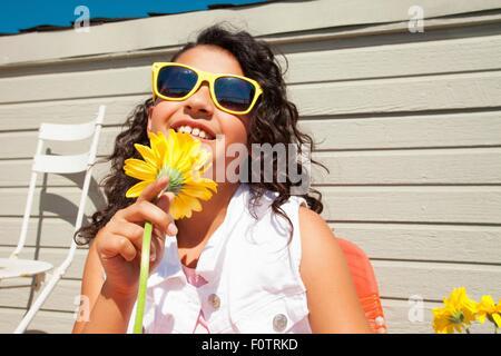 Ritratto di una ragazza indossando occhiali da sole giallo girasole di contenimento sul patio Foto Stock