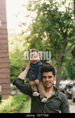 Bambino seduto sulla spalla dei padri, guardando alla fotocamera a sorridere Foto Stock