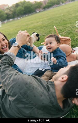 Padre, madre e bambino gioca con soft cane giocattolo Foto Stock