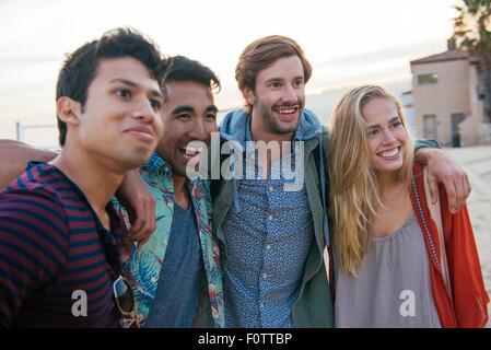 Gruppo di amici in piedi insieme sulla spiaggia, ridendo Foto Stock