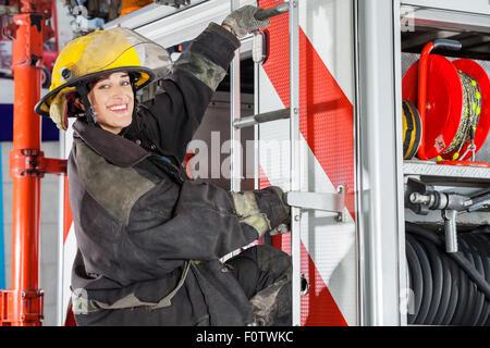 Firefighter sorridente in piedi sul carrello nella stazione dei vigili del fuoco Foto Stock