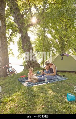 Madre e figli rilassante sulla coperta picnic in ambiente rurale Foto Stock