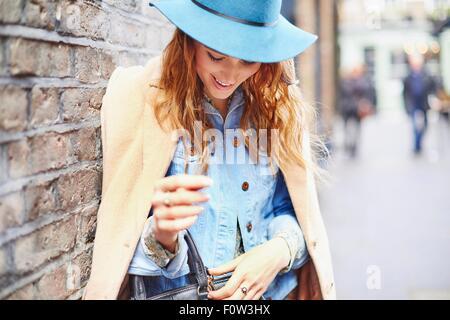 Elegante giovane femmina fissaggio shopper borsa di Londra, Regno Unito Foto Stock