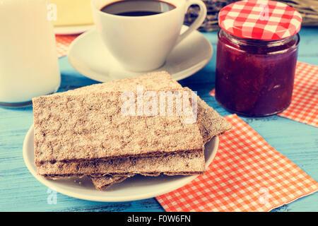 Primo piano di pani croccanti in una piastra, una tazza di caffè e una bottiglia di latte ed un vasetto di marmellata Foto Stock