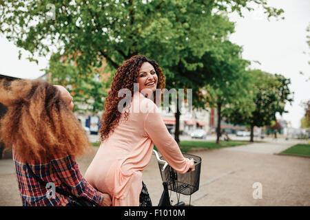 Ritratto di giovane e bella donna Bicicletta Equitazione con il suo amico. Amici di sesso femminile avente divertimento Foto Stock