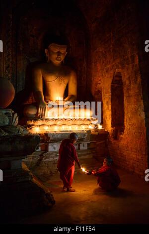 Asian monaci-in-formazione accendendo candele al santuario di Buddha Foto Stock